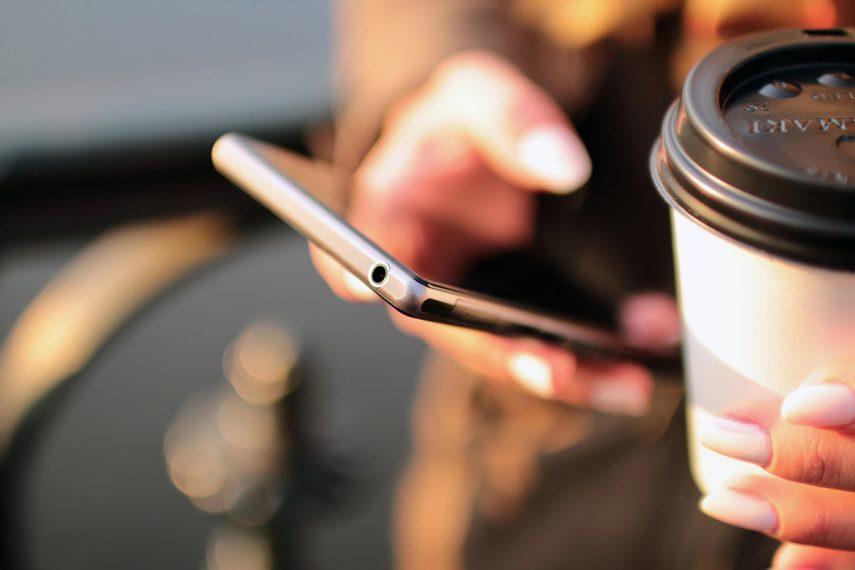 Hand mit Smartphone und Kaffeebecher
