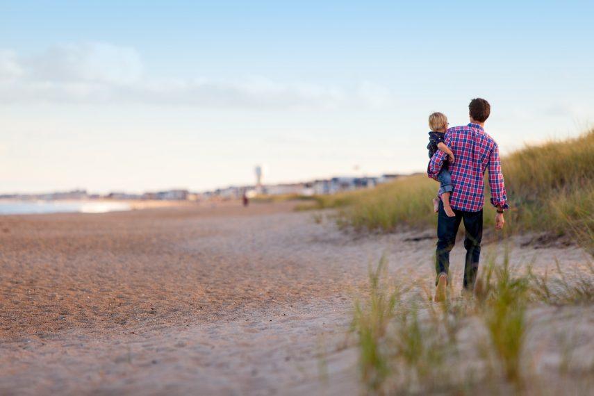 Junger Vater mit Kind auf dem Arm läuft an einem Strand