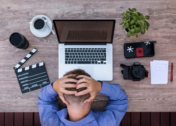 Mann sitzt an einem Schreibtisch und schlägt die Hände über den Kopf zusammen