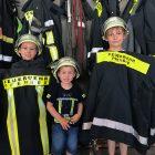 Drei Kinder halten Feuerwehrjacken in die Kamera