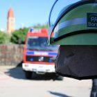 Spielzeugfeuerwehrhelm im Vordergrund - Feuerwehrauto im Hintergrund