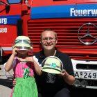 Mann mit Kind und gesponsorten Spielzeugfeuerwehrhelmen