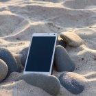 Smartphone liegt im Sand an einem Strand