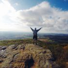 Wanderer steht auf Berggipfel