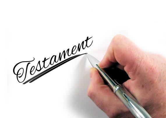 Hand mit Stift schreibt Testament