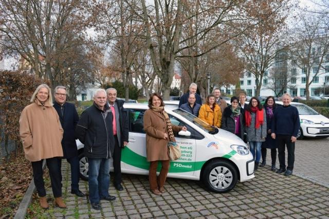 Gruppe mit Personen steht auf dem Parkplatz der PSD Bank München